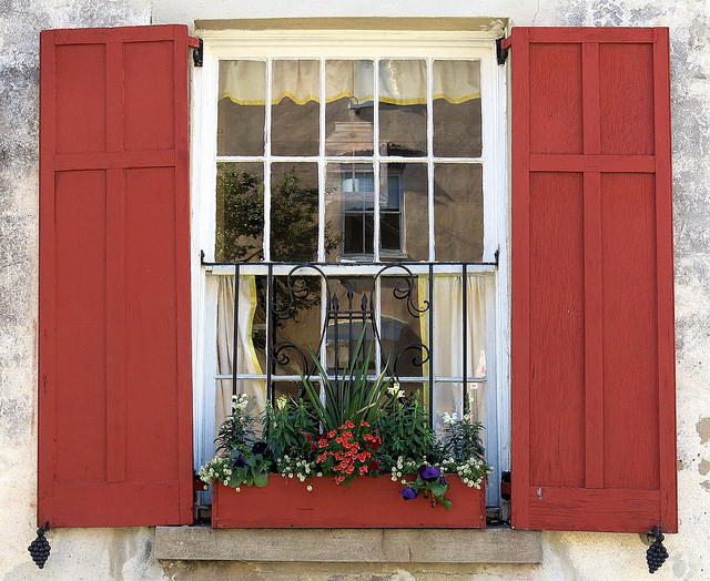 window with orange red shutters and window box