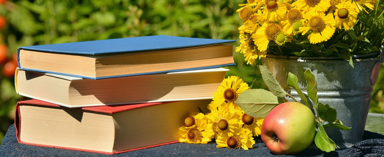 books, flowers and an apple on top of a table